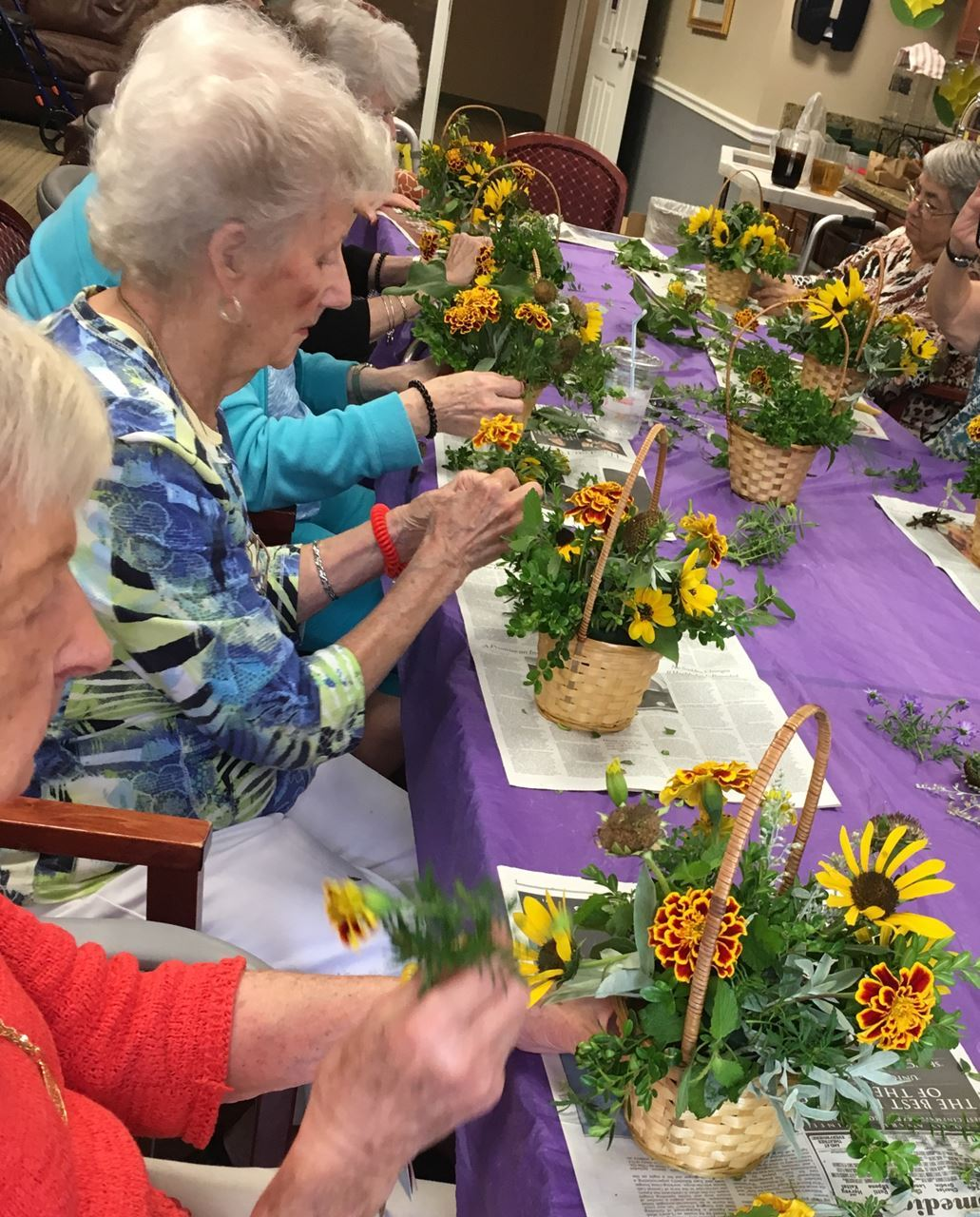 Senior citizens in a horticulture therapy session making fresh flower arrangements.